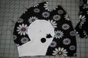 sew polar fleece penguin eye on by hand before 2 sides of head are attached