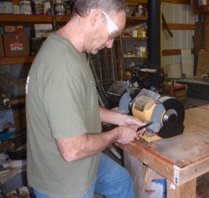 using his grinder to file off sharp edges from the cut metal