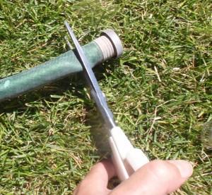 using Cutco scissors to remove the broken hardware on the hose