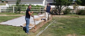 2 hard working young men carefully dig a trench through my lawn for the underground wires