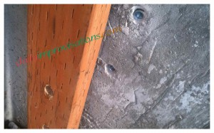 The pre-drilled holes in the cement and wood.