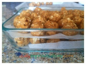 Peanut butter snack balls layered with wax paper to keep them from sticking together while in the refrigerator.