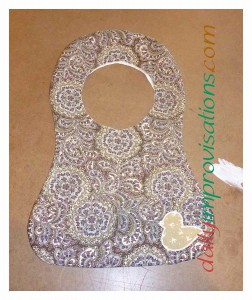 The paisley side of the bib after the outer edges have been sewn and the bib is turned right sides out.