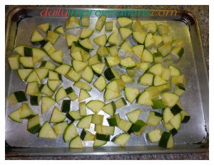 The still raw zucchini in a single layer on a half sheet pan.