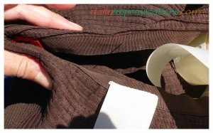 I determined that the tag marked the back of the hat, then folded it to make sure the ties were aligned equally on both sides.