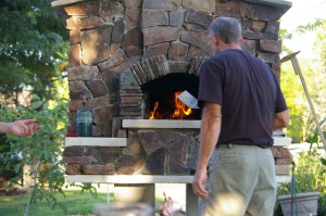 Greg cooking brick oven pizza before he has the final logo piece at the top of the door arch.